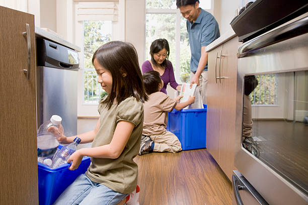family in kitchen recycling paper and plastic - recycling symbol stock photos and pictures