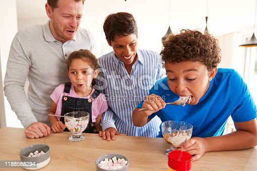 Family In Kitchen With Children Making And Eating Ice Cream Desserts