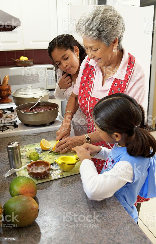 Family in kitchen, with granddaughters (6-12) watching grandmother slice citrus fruit stock photo