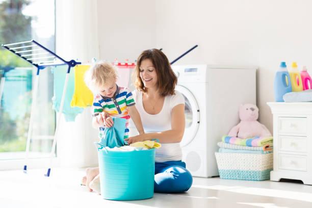 family in laundry room with washing machine - стирка стоковые фото и изображения