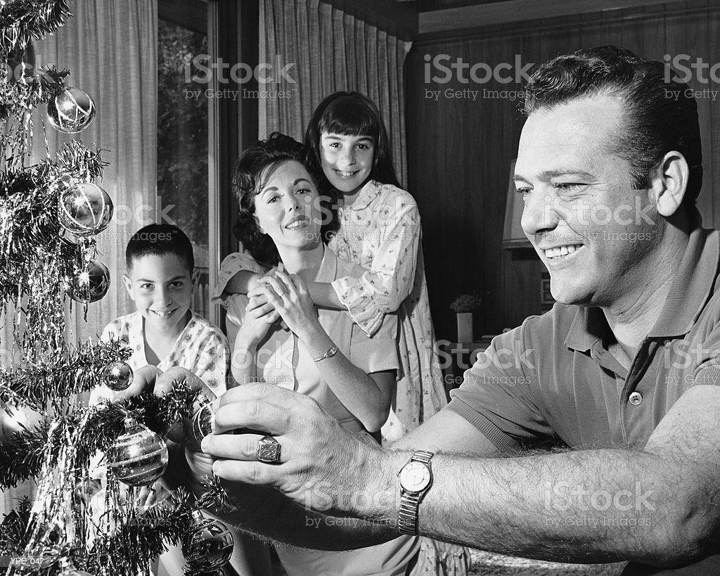 Family in living room, father decorating Christmas tree royalty-free stock photo