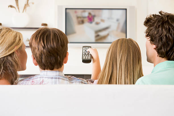 family in living room watching tv - family watching tv stock photos and pictures