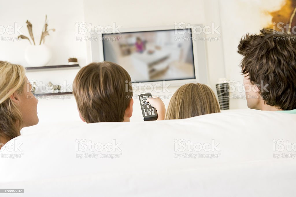 Family in living room with remote control and television stock photo