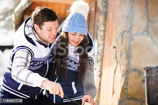 istock Family in love laughing and cooking in the winter outdoors. Bonfire, barbecue, bowler. 1184647278
