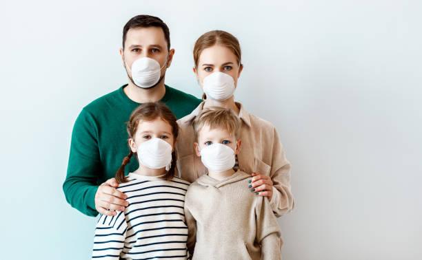 Familie in medizinischen Masken während Desseausbruch – Foto