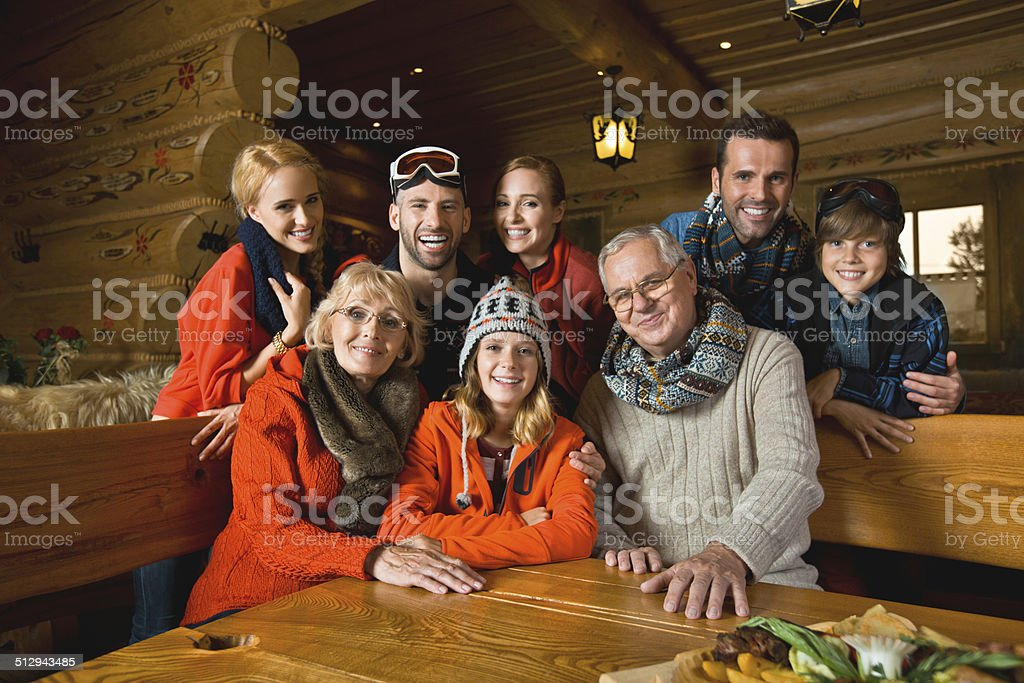 Family in mountain restaurant Portrait of multi-generation family sitting in a mountain restaurant after skiing, smiling at the camera. Active Seniors Stock Photo