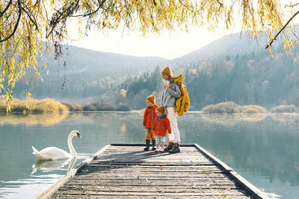 Family in nature background. Mother and children together in countryside outdoors. stock photo