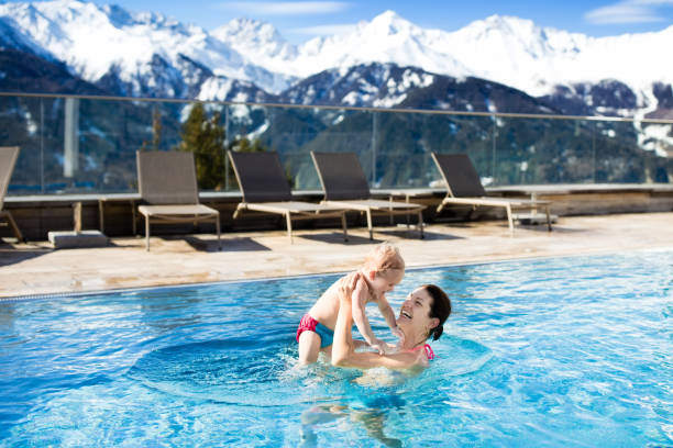 familie im außenpool des alpine spa-resorts - hotel in den bergen stock-fotos und bilder