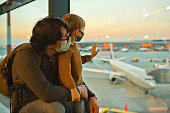 istock Family in protective face masks in airport during COVID-19 pandemic 1284745836