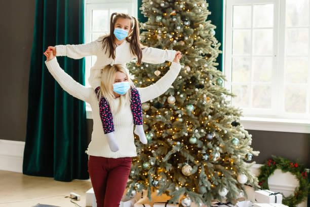 family in protective masks quarantined. Normal life with coronavirus. Lifestyle COVID-19. Quarantine virus protection. christmas stock photo