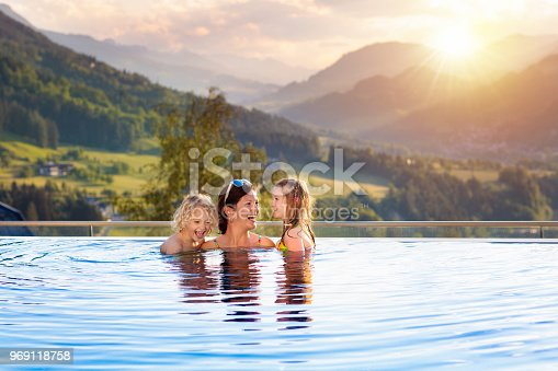 istock Family in swimming pool with mountain view 969118758