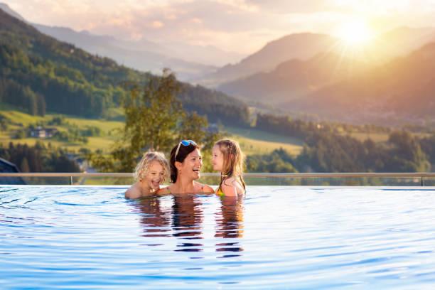 familie im swimmingpool mit blick auf die berge - hotel in den bergen stock-fotos und bilder