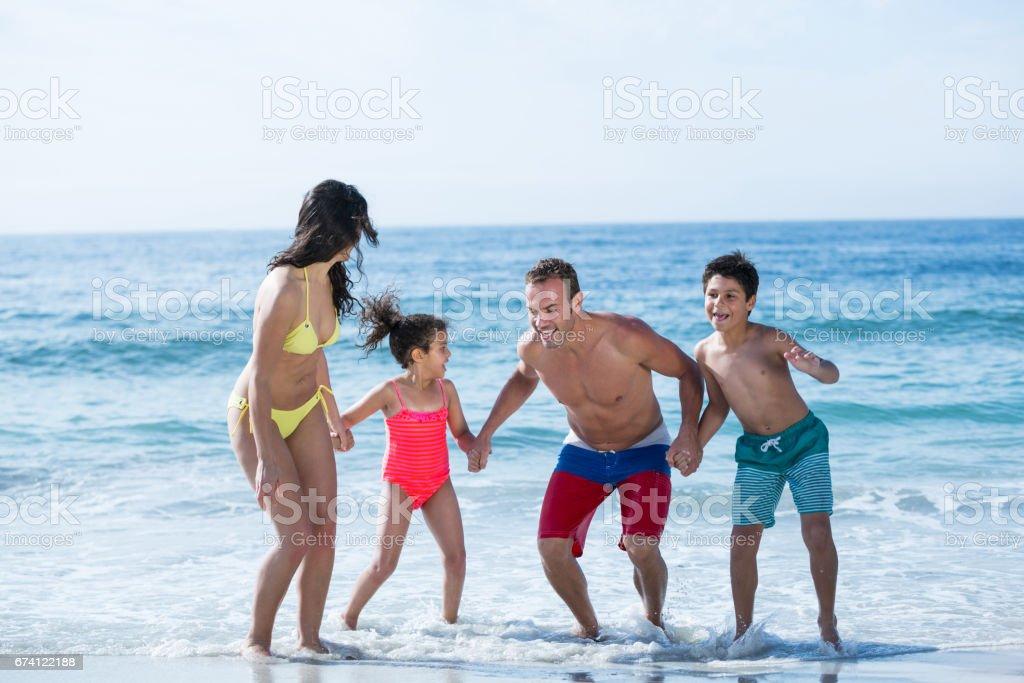 家庭在泳裝手牽著手在享受的同時 免版稅 stock photo