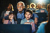Close up of grandfather taking his grandchildren to the cinema