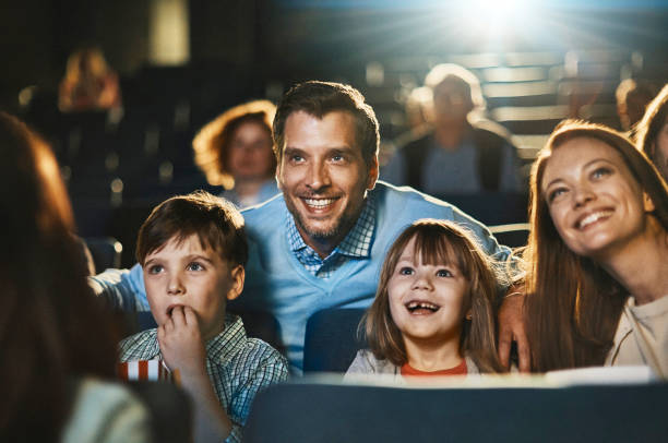 Family in the cinema Close up of a young family enjoying a movie in the cinema movie theater stock pictures, royalty-free photos & images
