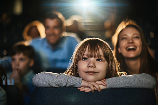 Close up of a young family enjoying a movie in the cinema