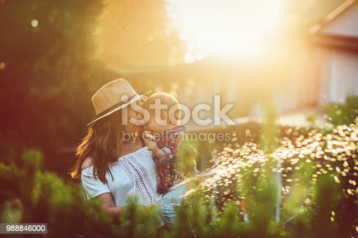 Mother and her little sun watering plants in garden in summer