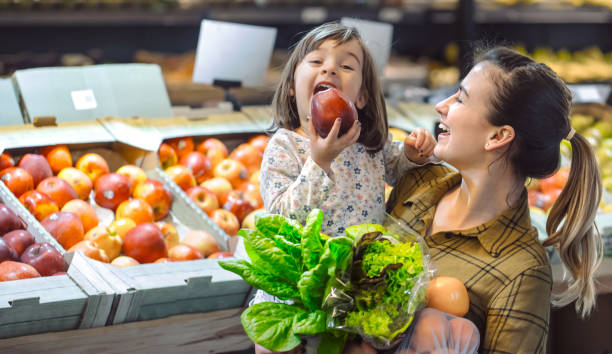 family in the supermarket. beautiful young mom and her little daughter smiling and buying food. - vendas imagens e fotografias de stock