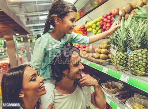 Beautiful young parents and their cute little daughter are talking and smiling while choosing food in the supermarket. Girl is sitting on dad's shoulders