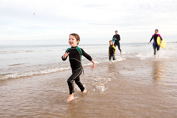 Family in Wetsuits Family of four are running along the shore with body boards. They are all laughing. wetsuit stock pictures, royalty-free photos & images