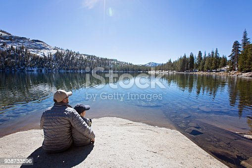 family of two, father and son, sitting and enjoying beautiful tenaya lake at tioga pass in yosemite national park, active vacation concept