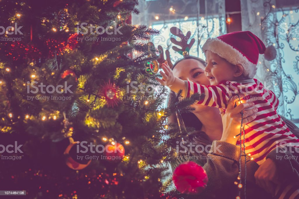 Family indoors near Christmas tree stock photo