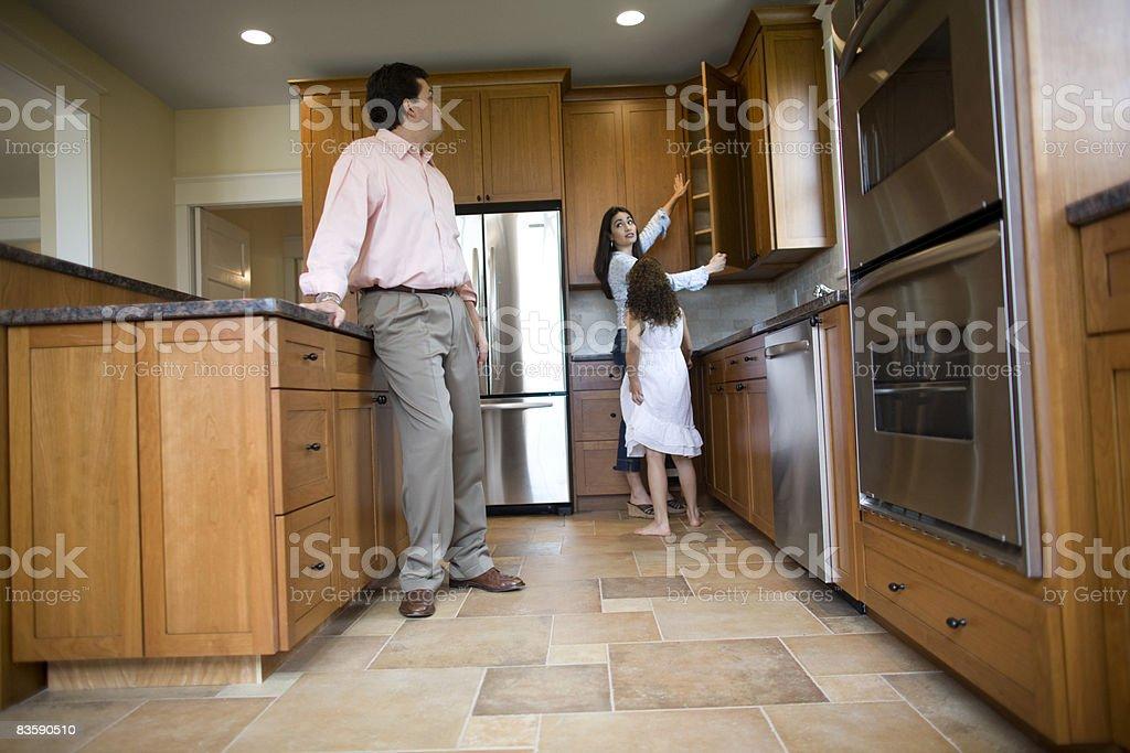 Family inspecting kitchen in house for sale royaltyfri bildbanksbilder