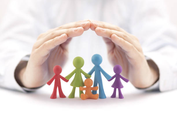 Family insurance concept with colorful family figurines covered by hands stock photo