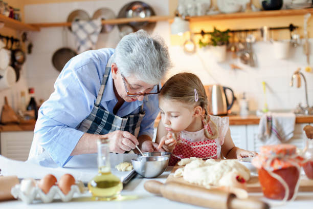Family is cooking in cozy kitchen at home. Grandmother and child are making italian food and meal. stock photo