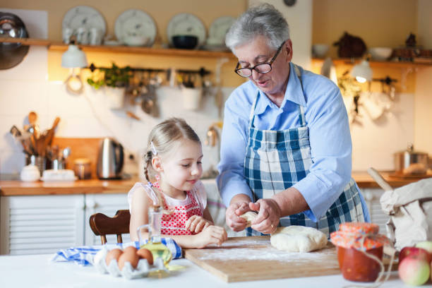 Family is cooking in cozy kitchen at home. Grandmother is teaching little girl. Senior woman and child make pastry dough stock photo