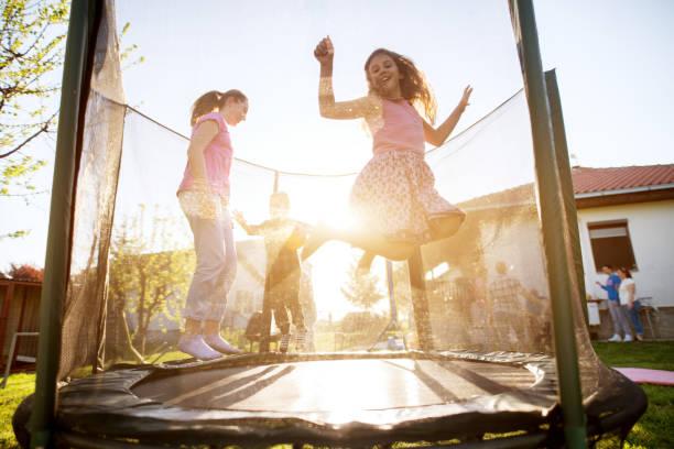 familie hat einen chat, während drei liebenswert verspielten kinder unruhig auf trampolin springen. - gartentrampolin stock-fotos und bilder