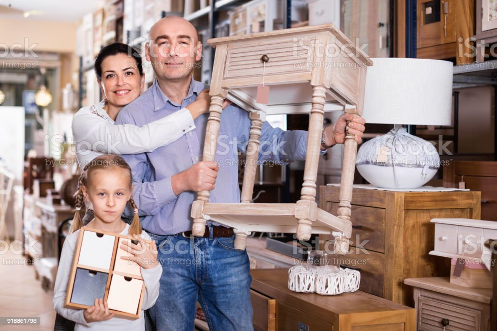 Family is holding new curbstone that their choosing for bedroom in the furniture store. stock photo