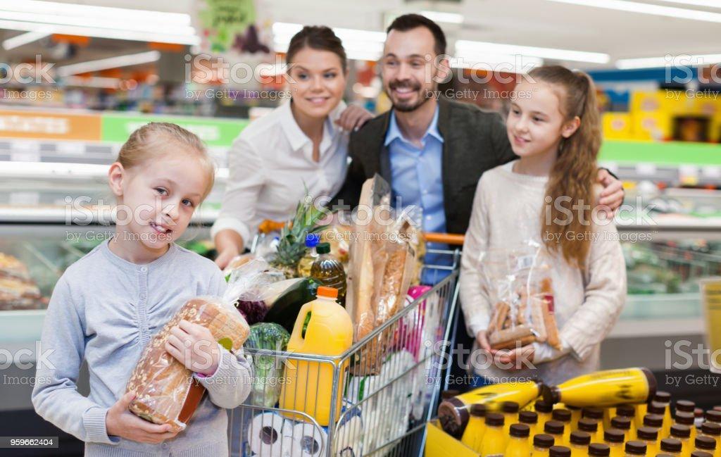 Familia está de pie con el carro con los productos en el supermercado. - Foto de stock de Adulto libre de derechos