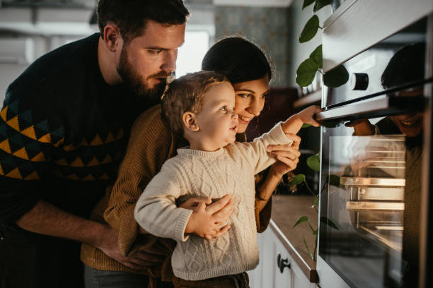 Family is waiting for meal to be done Young family with son is looking in the oven and waiting for their meal to be done. oven stock pictures, royalty-free photos & images