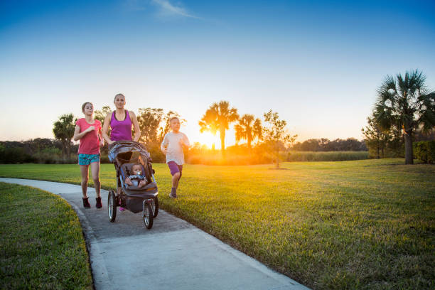 Family jogging and exercising outdoors together stock photo
