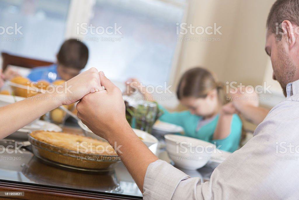 Family joining hands to pray over meal at dinner table stock photo