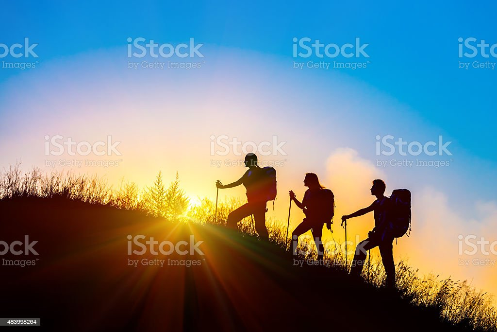 Silhouettes of three people walking with backpacks and other hiking...