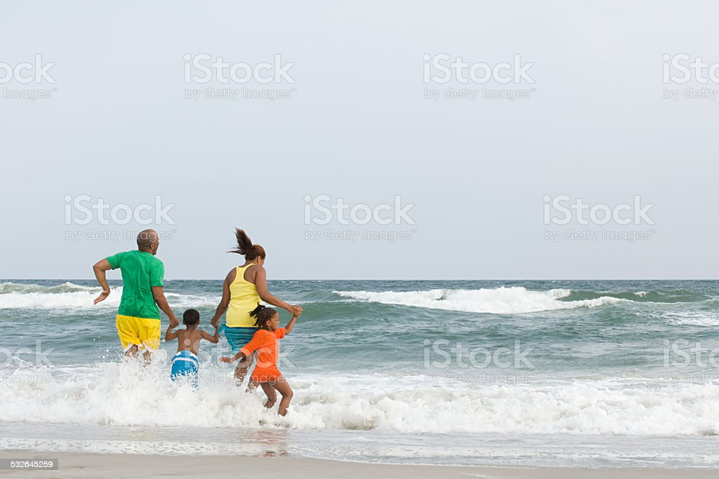 Family jumping in the sea stock photo