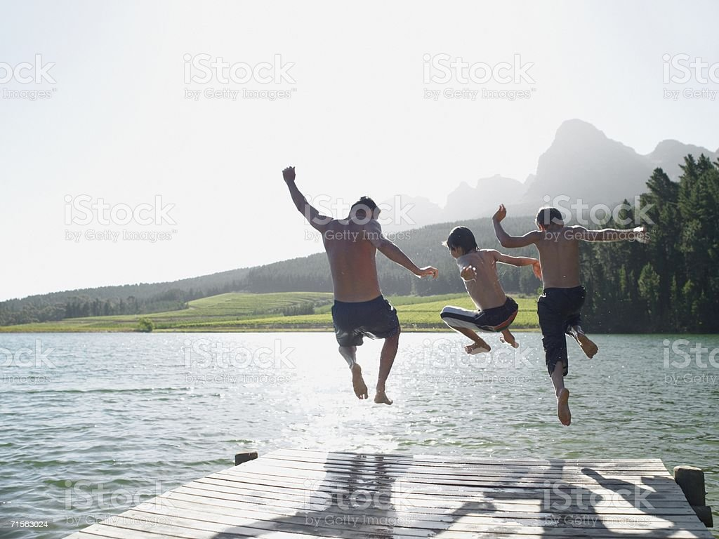 Family jumping into fijord stock photo