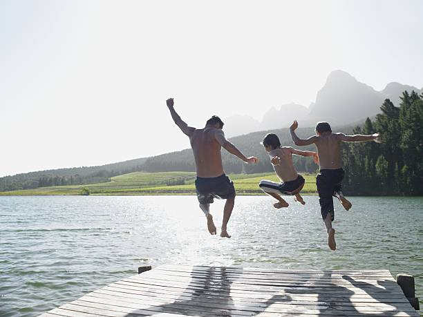 Family jumping into fijord stock photo