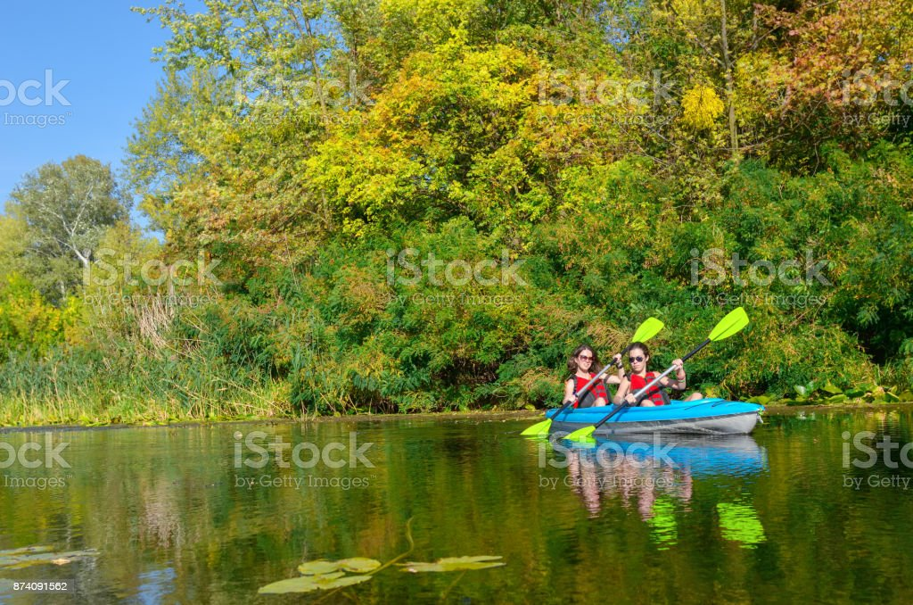 Family kayaking, mother and child paddling in kayak on river canoe tour, active autumn weekend and vacation, sport and fitness concept stock photo