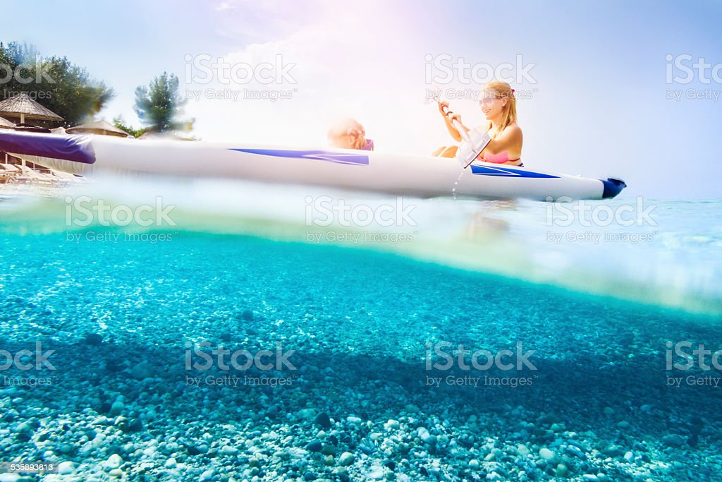 Family kayaking on beautiful beach stock photo