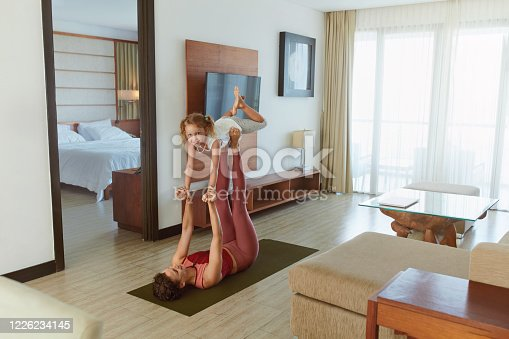 916126642 istock photo Family. Kid And Mother Practicing Partner Yoga At Home. Young Woman And Daughter Exercising Together. Sporty Parent And Child Doing Acroyoga In Living Room. 1226234145