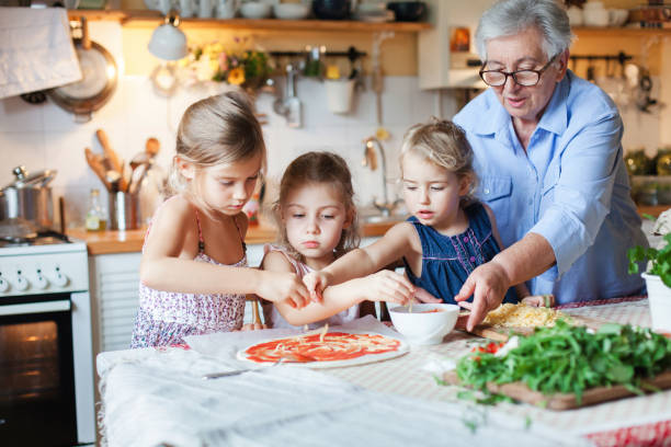 Family, kids cooking pizza in cozy home kitchen. Grandmother and three sisters, her granddaughters preparing homemade italian food. Funny little girls are helping senior woman. Children chef concept. stock photo