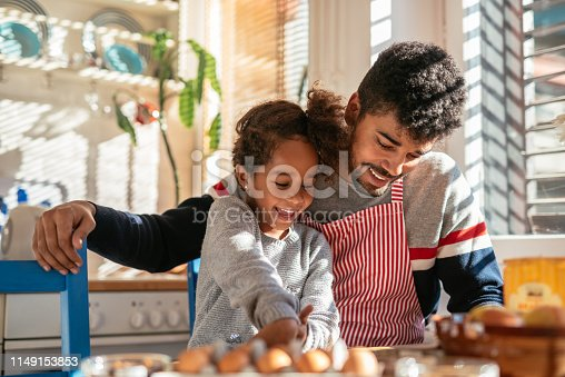 African american father and his daughter sitting in the kitchen and reading a recipe. Dad is wearing an apron. They are both happy.