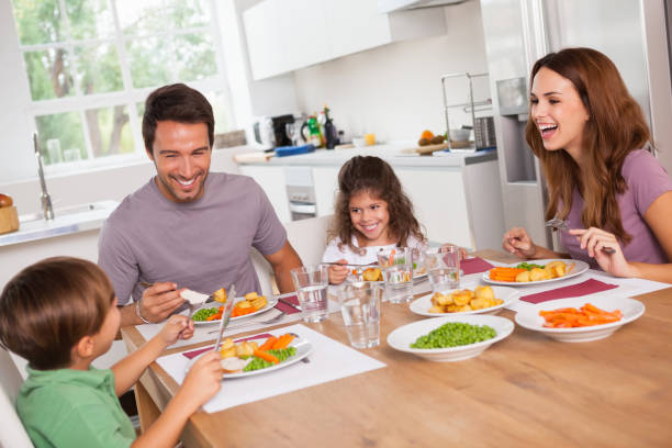 family laughing around a good meal - family dinner stock photos and pictures