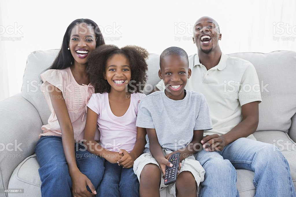 Family laughing at the tv on couch royalty-free stock photo