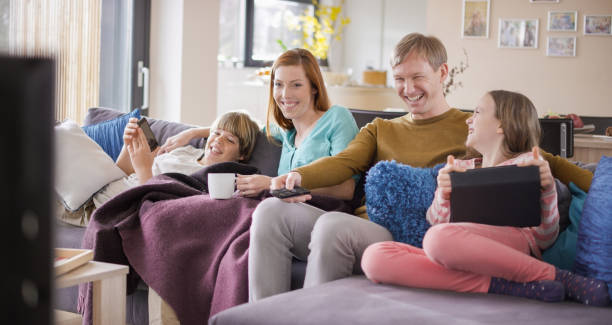 Family laughing while watching TV on sofa stock photo
