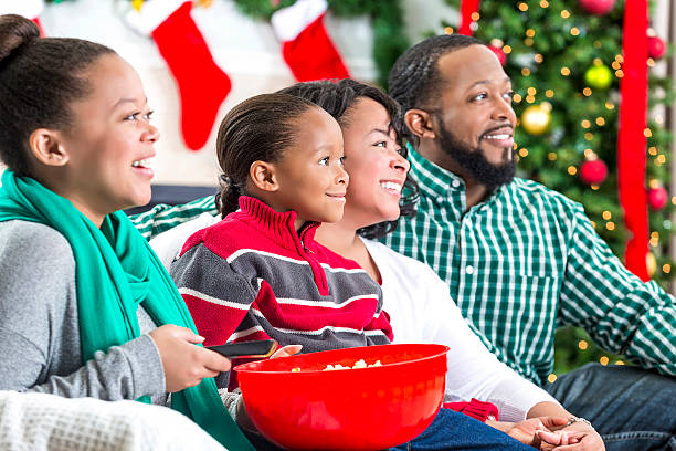 family laughs while watching christmas movie - christmas movie foto e immagini stock