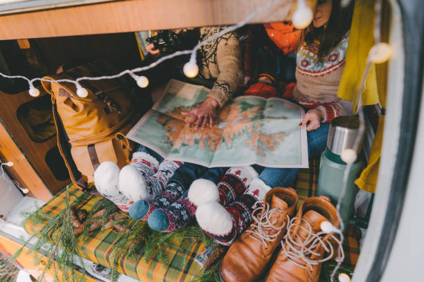 Family laying in camper van in Christmas socks  and looking at map Family with little boy laying in camper van in Christmas socks rv interior stock pictures, royalty-free photos & images